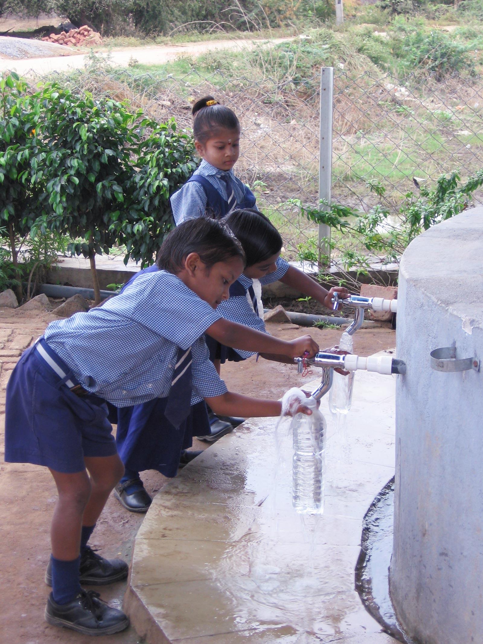 School children picking up drinking water.