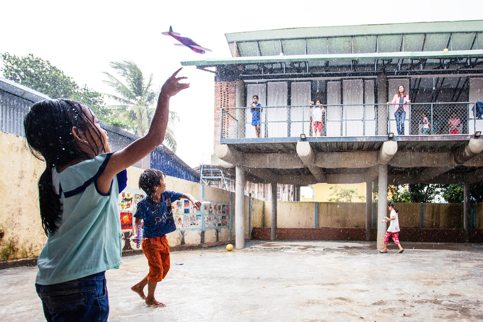 Children playing at the Bomnong L'or Community Centre in Cambodia. The Centre sits on a dense urban site and is contructed out of fabric-formed post and beam concrete, engaging local female tailors, and is raised up similar to traditional wooden Khmer houses to create a large playground underneath. Image Credit: Lindsay Perth