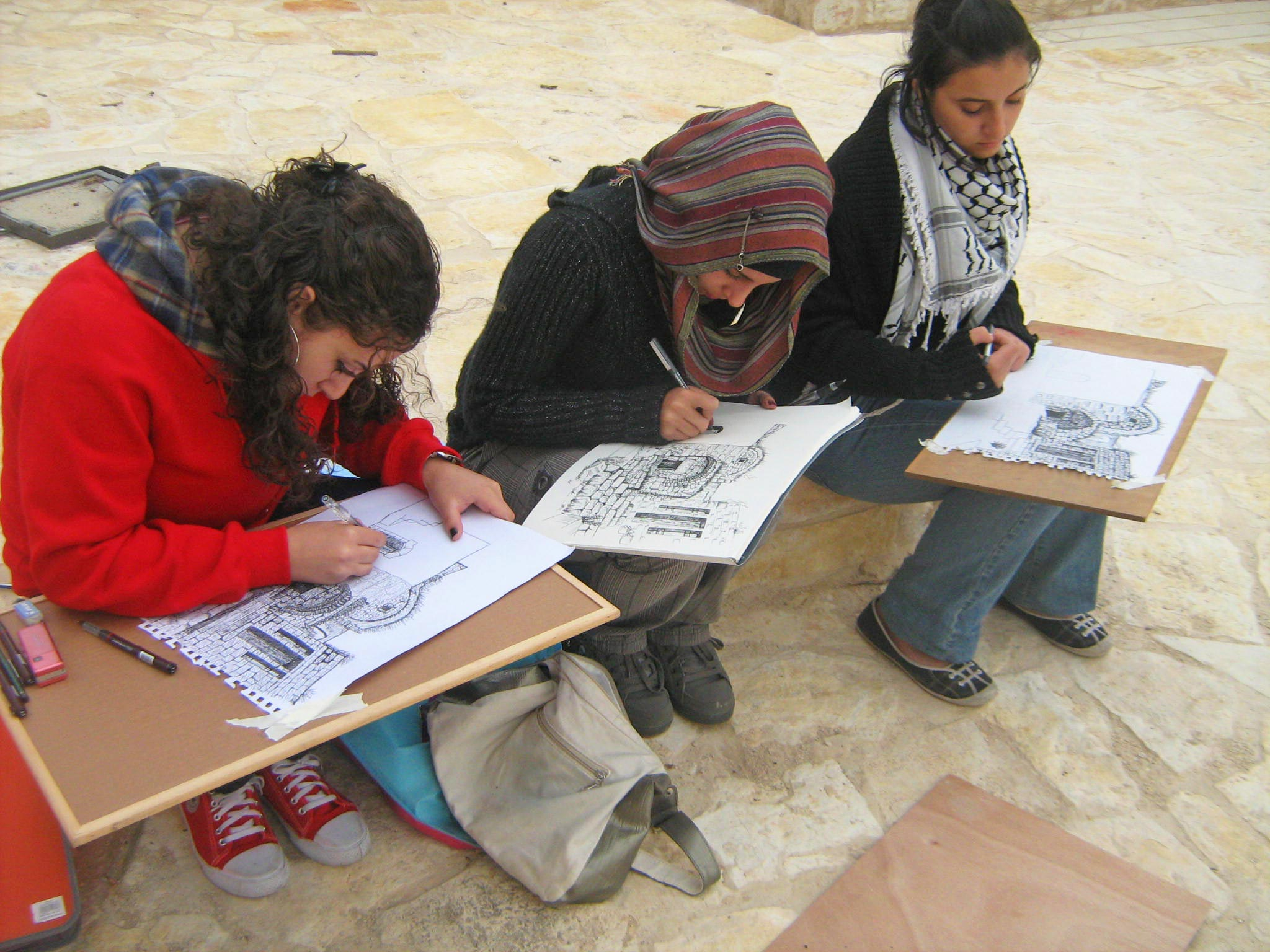 University students sketching buildings for a Riwaq competition. Organized by Riwaq, the Tom Kay Award supports Palestinian engineering students with the aim of encouraging them to spend less time in front of computer screens, and to carry their sketchbooks and pencils to explore, appreciate, draw, and document Palestinian architectural heritage. Image Credit: Riwaq Photo Archive